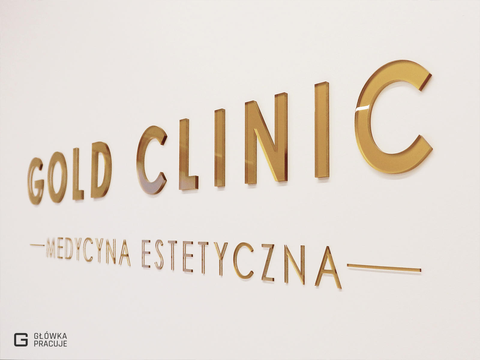 Główka pracuje pl Gold Clinic logotyp z plexi bezbarwnej podklejonej złotą folią, gabinet