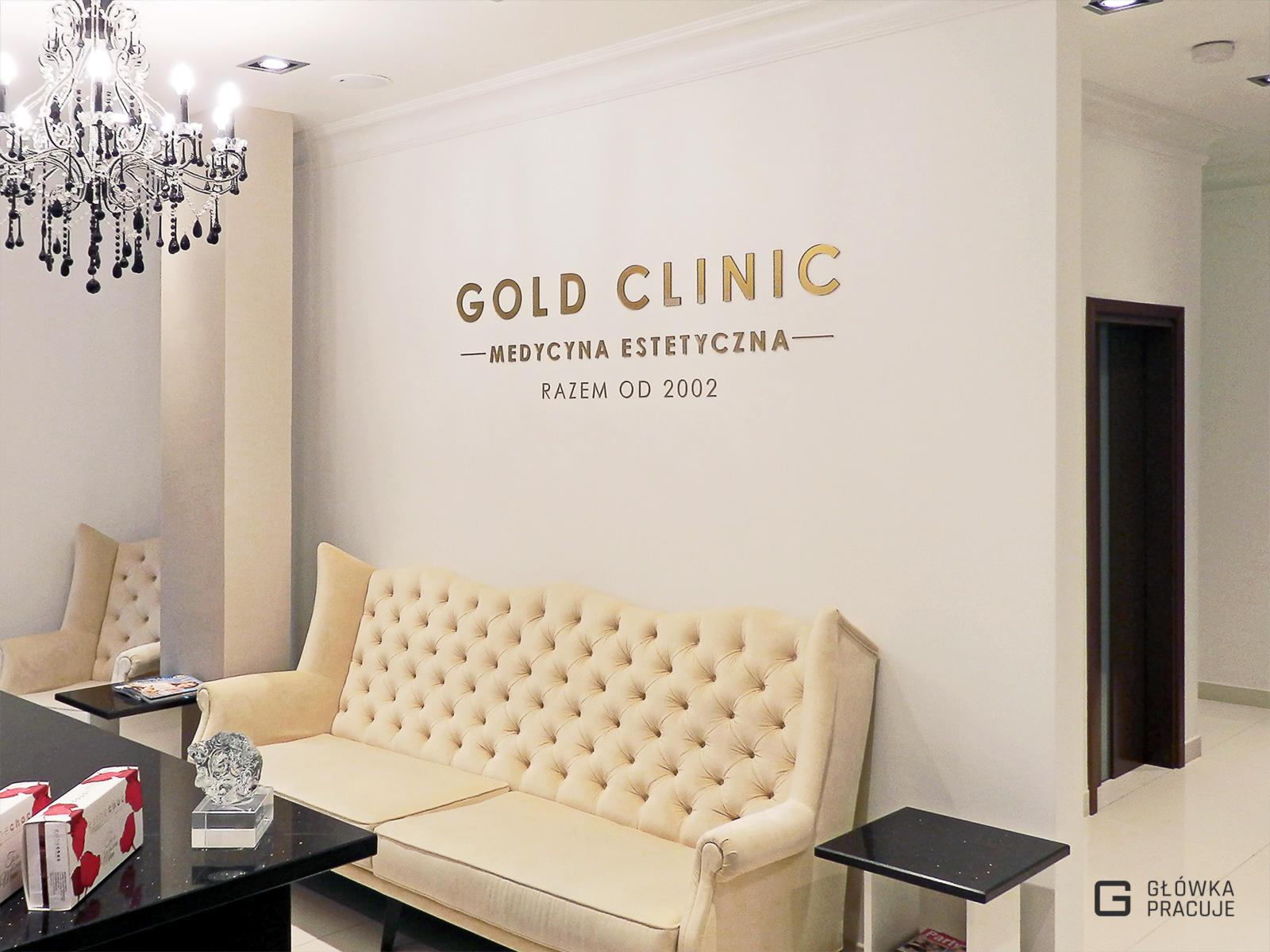 Główka pracuje pl Gold Clinic logotyp z plexi bezbarwnej podklejonej złotą folią, recepcja