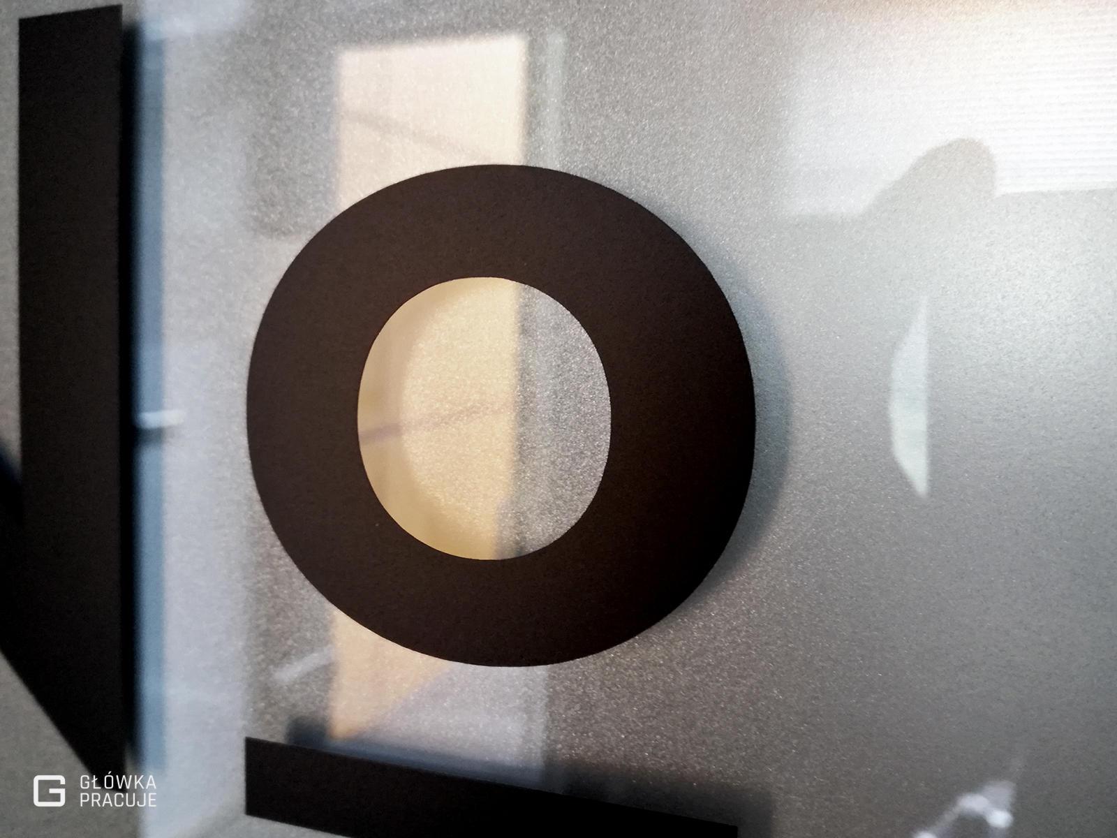 Główka Pracuje pl Number Coffee logotyp wycięty z czarnej folii naklejony na szklane drzwi z matową folią