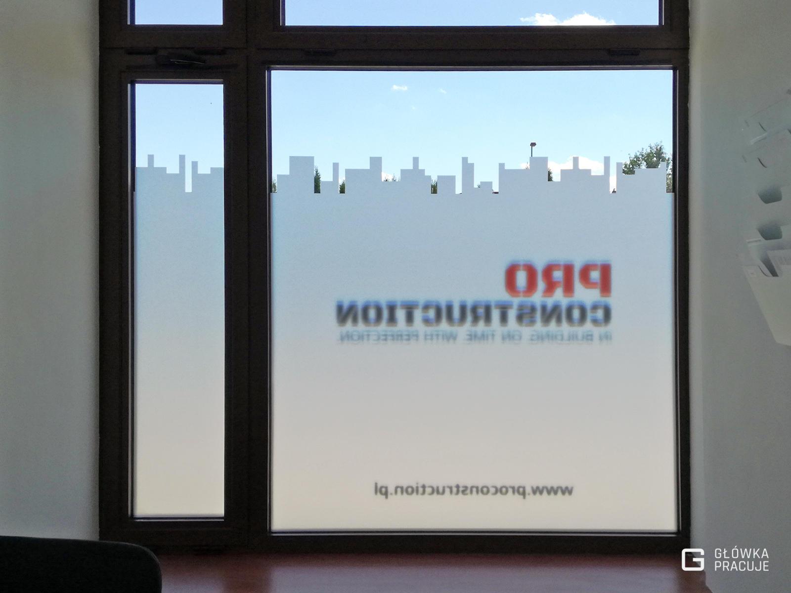 Główka pracuje pl Pro Construction folia okienna matowa na witrynie i kolorowy logotyp widok od wewnątrz Warszawa