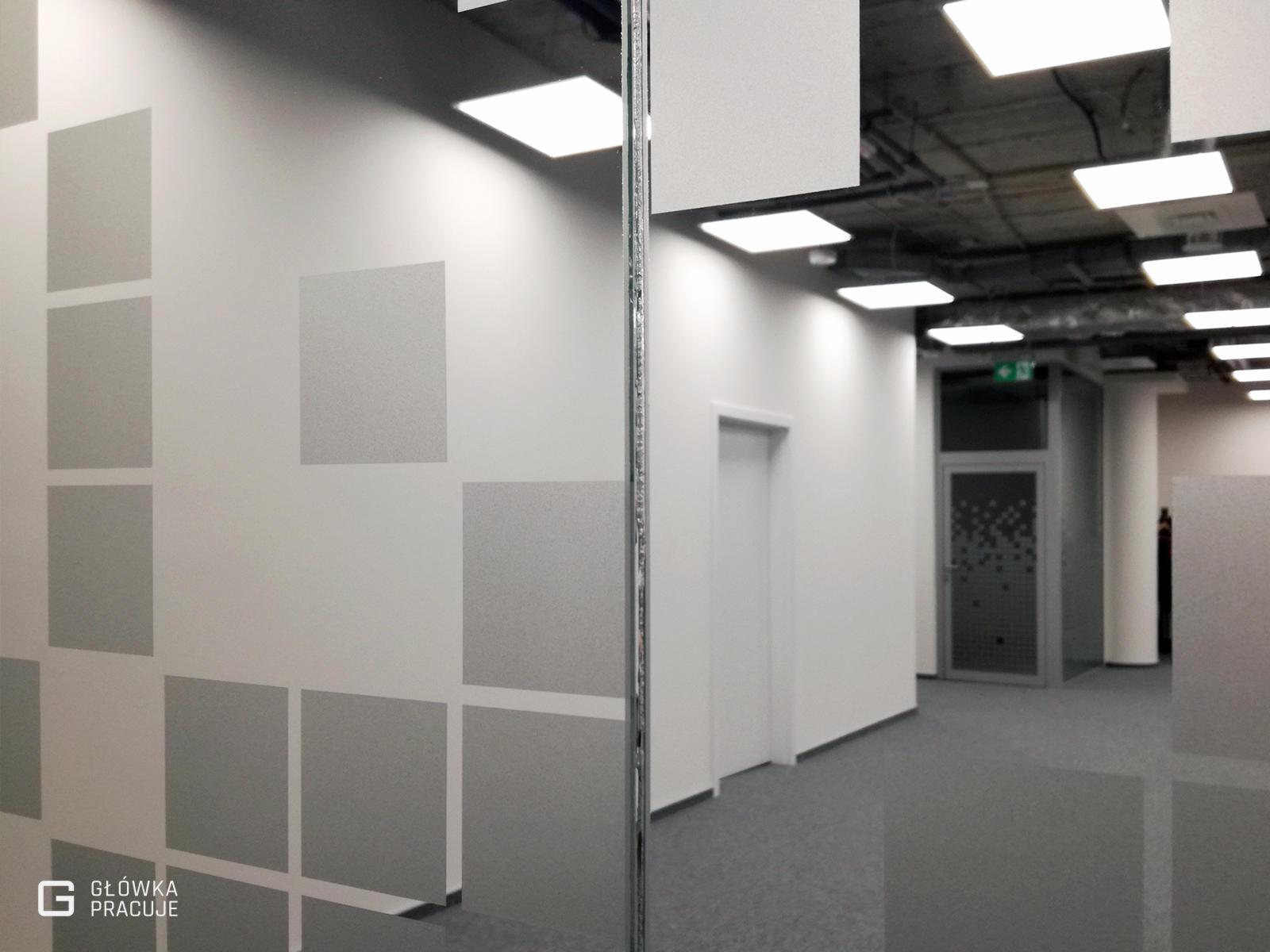 Główka Pracuje - folia mrożona z wyciętymi pikselami na szklaną ściankę w biurze - Warszawa