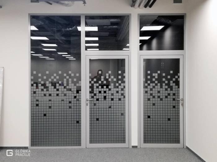 Główka Pracuje - matowa szroniona folia z wyciętymi kwadratami na ściance szklanej w biurze - Warszawa